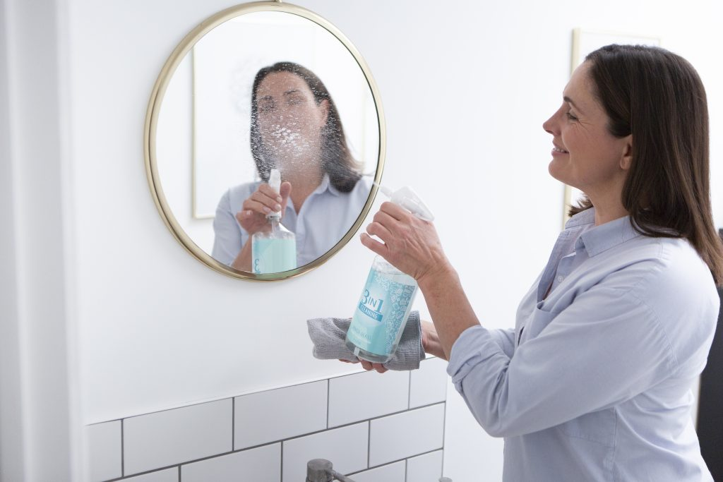 Woman spring cleaning a mirror